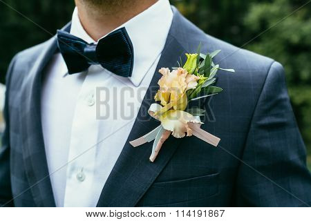 Wedding Boutonniere On Chequered Suit Of Groom With Bow-tie