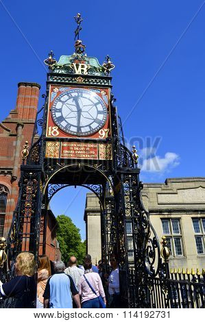 Tourists walking along Chester wall at Eastgate clock t