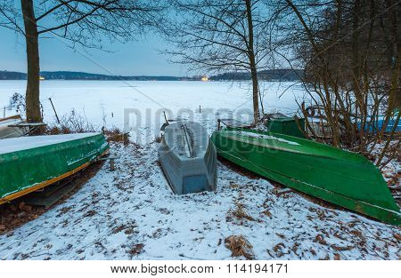 Fisherman Boats On Frozen Lake Shore. Winter Landscape