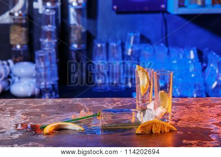 The spilled cocktails with ice cubes on blue color in the bar