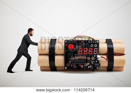 small businessman in formal wear pushing big bomb with timer over light grey background