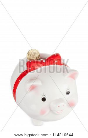 White Pig Moneybox With A Coin Isolated On A White Background