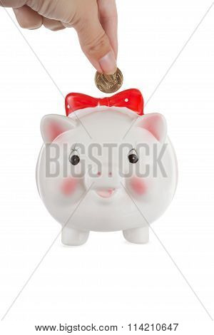 Hand Puts A Coin In A Piggy Bank, Isolated, White Background