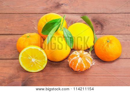 Several Mandarin Oranges, Lemons And  Oranges On A Wooden Surface