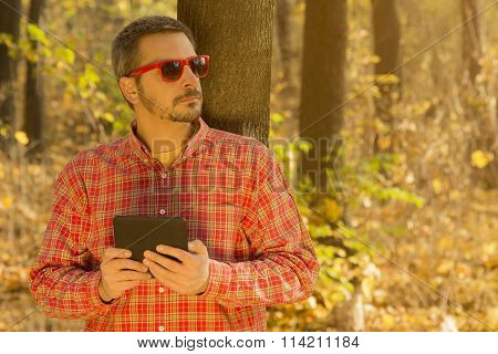 Man with a digital tablet leaning against the tree
