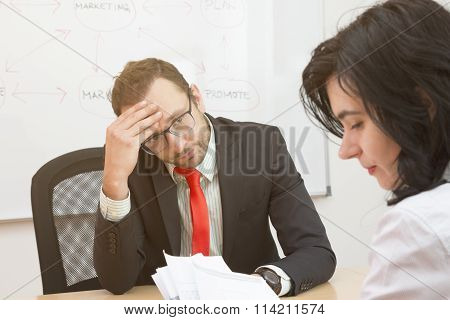 Unsatisfied boss and sad female worker