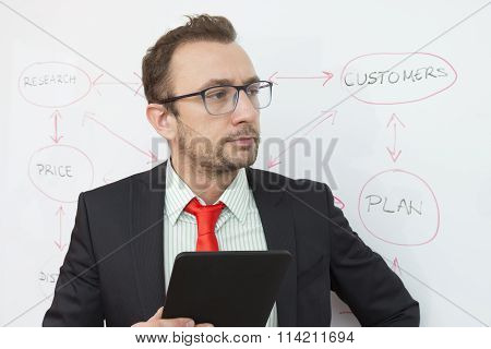 Business expert holding digital tablet device. Flowchart in the background