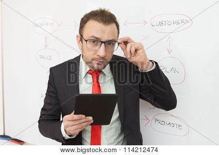 Portrait of a businessman with a digital tablet. Flowchart in the background.