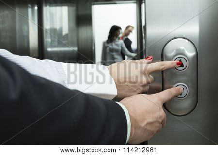 Female and male forefingers pressing elevator buttons to different directions. Mirror reflection.