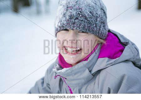 Little girl in winter season with hat in snow.