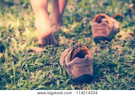 Child Take Off Shoes. Child's Foot Learns To Walk On Grass
