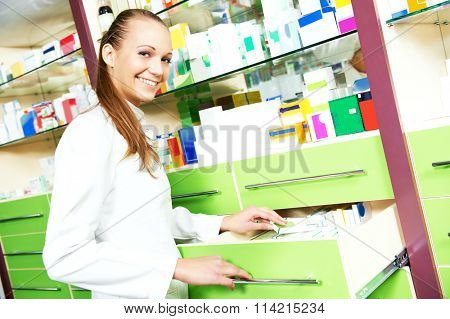 cheerful smiling pharmacist woman standing in pharmacy drugstore