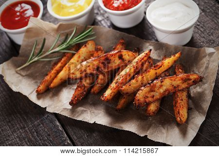 Spicy roasted potato wedges with salsa dip, mustard and relish