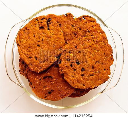 Indian savouries kept on transparent glass bowl on a plain background