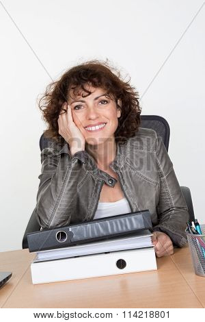 Frustrated Business Woman In Office Looks At Unbelievable Folder Stack.