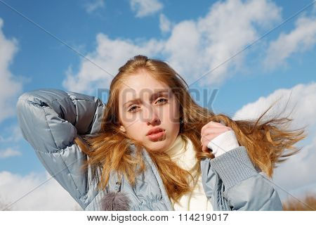 Girl In Jacket On Blue Sky Background