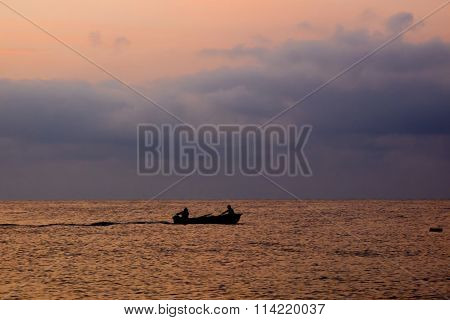 Fishermen on a boat at sunrise before storm