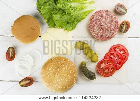 Ingredients For Burger: Meat, Roll With Sesame, Cheese, Lettuce, Onions, Tomatoes On A White Wooden