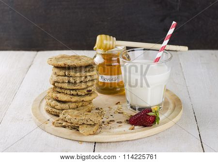 Granola With Nuts In Glass Jar, Strawberry, Honey Jar, Pile Of Oatmeal Cookies On White Wooden Table