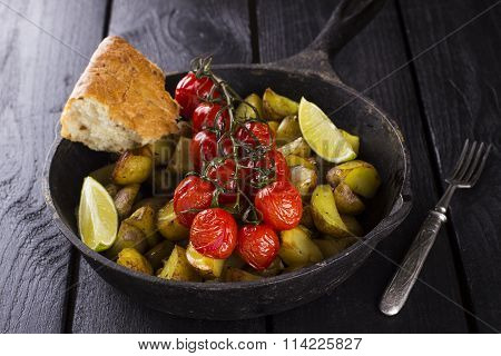 Frying Pan With Fried Potato And The Baked Cherry Tomatoes On Branch, Lime Segments With Piece Of Br