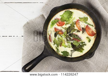 Omelet With Tomatoes And Lettuce In Black Frying Pan On Linen Napkin, White Wooden Background. Top V