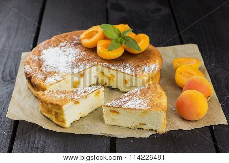 Slices Of Pie With Cottage Cheese, Apricots And Icing Sugar On A Brown Wooden Background