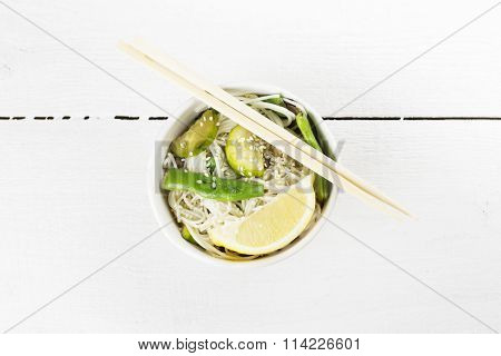 Asian Noodles With Siliculose Haricot, Zucchini And Lemon On White Wooden Background. Top View