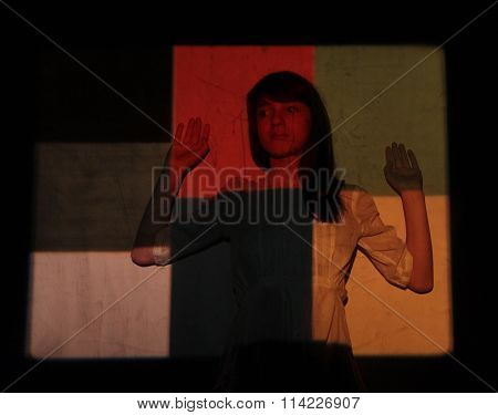 The girl on the background of colorful backgrounds - in the light of the projector