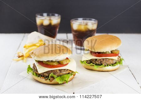 Two Mini Burgers With Meat, Lettuce, Tomatoes, Cheese, Pickles, Onions, French Fries And Sparkling W