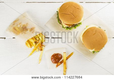 Mini Burgers With French Fries And Ketchup On A White Wooden Background. Top View