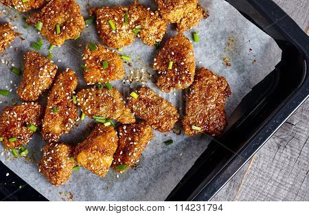 Chicken nuggets in sticky honey sauce on a wooden background