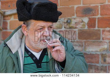 Portrait of a bearded Ukrainian peasant with cigarette