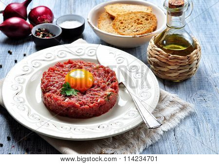raw beef steak tartare with egg yolk, red onion, capers, spicy sauce, sea salt, pepper and olive oil