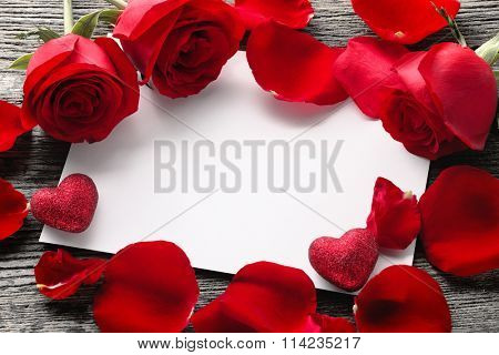 Valentine's Day Concept: White empty paper card, roses and roses petals on rustic wooden background.