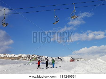 Three Skiers On Slope At Sun Nice Day