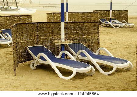 Blue Sun Loungers On The Beach.