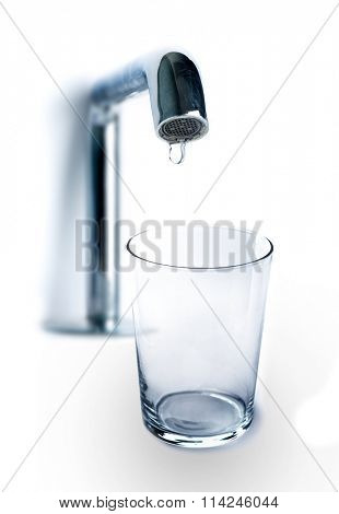 One drop of water dripping from the tap in an empty glass on white