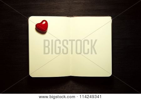 Blank Notebook With Heart On Black Background