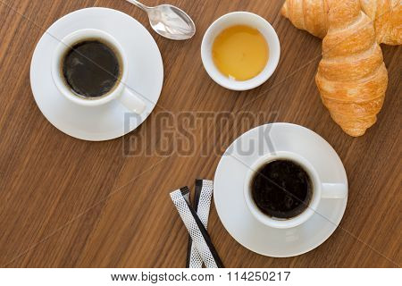 Two cups of coffee with croissants, honey and sachets sugar on  wooden table. top view