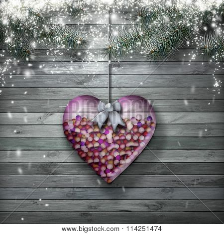 glass heart filled with candy on a snowy background