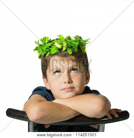 Very beautiful seven year old boy in a carnival wearing a crown of shiny green leaves. He sits astride a chair