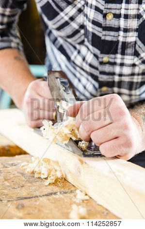 Close-up of carpenter work with plane on wood plank
