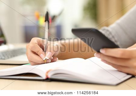 Woman Hand Writing In Agenda Consulting Phone
