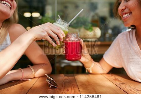 Two Happy Women Enjoying Fresh Drinks At Cafe