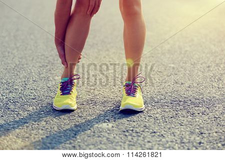 young fitness woman runner hold her injured leg