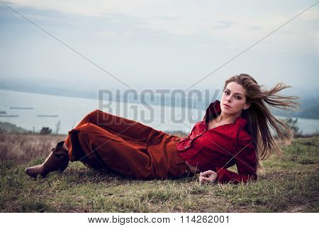 young blonde fashion girl lie on top of hill wearing long brown skirt and red leather jacket full body shot