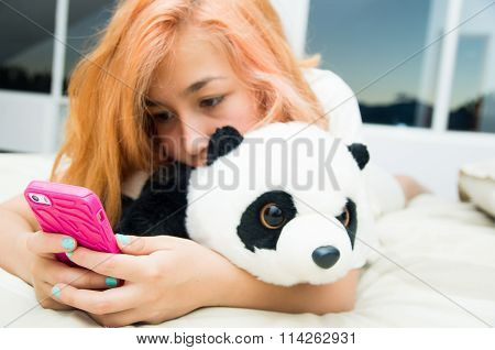 Pretty young woman lying comfortably on bed hugging stuffed panda animal and using pink mobile phone