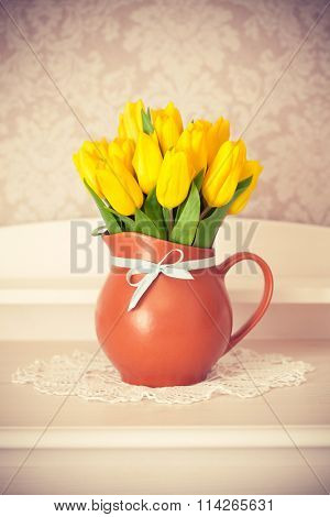 bunch yellow tulips in jug on wooden table. Rasterized illustration.