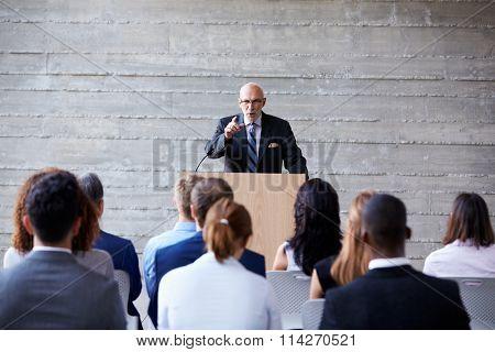 Senior Businessman Addressing Delegates At Conference