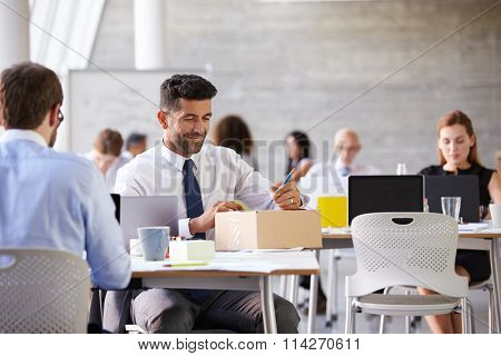 Businessman In Office Addressing Package For Shipping